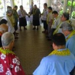 Delegation of overseas Samoan pastors praying with Samoa-Tokelau Mission leaders in meeting at Mission headquarters